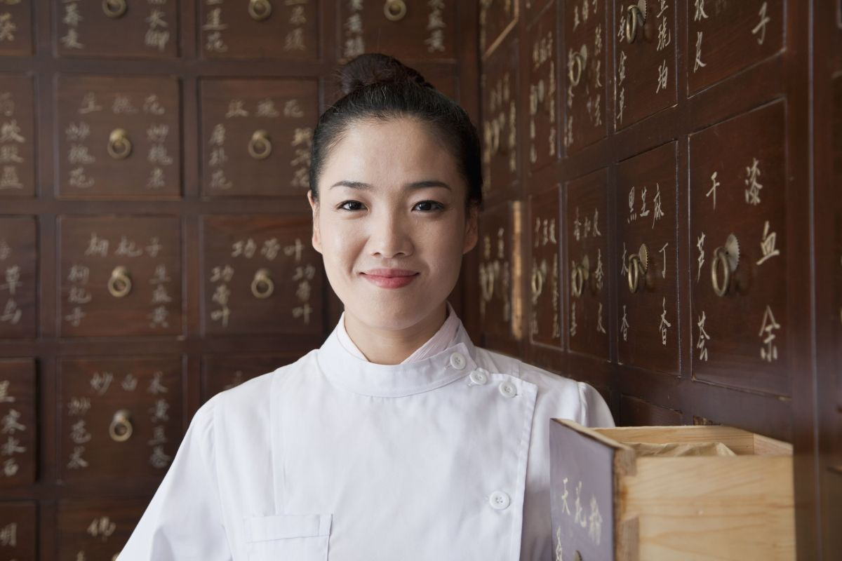 portrait of doctor in front of traditional chinese medicine cabinet - integrative medicine