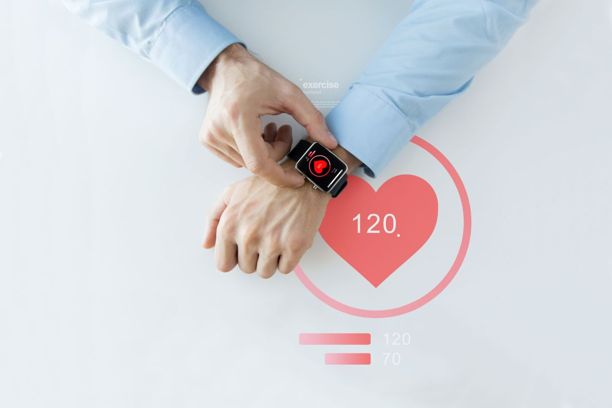 close up of hands with heart icon on smart watch - cut cost concept