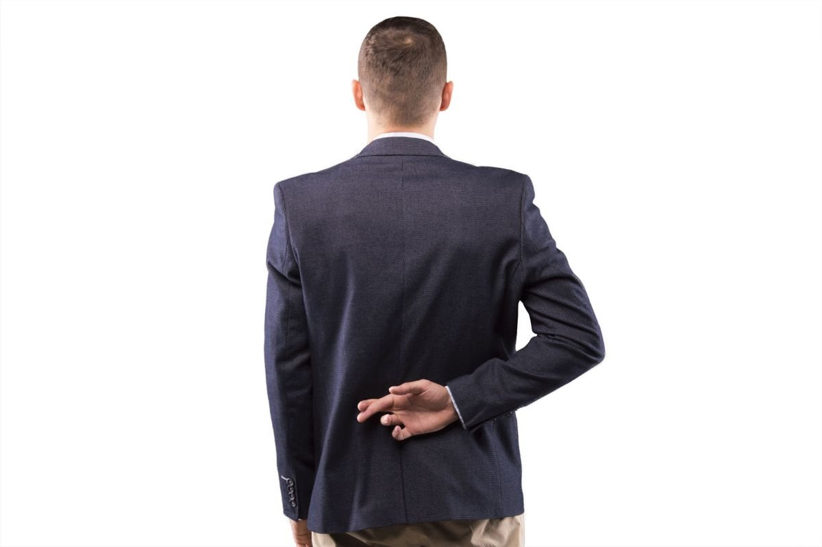 Man in a suit crossed his fingers behind his back, representing the problems with clinical trial incentives