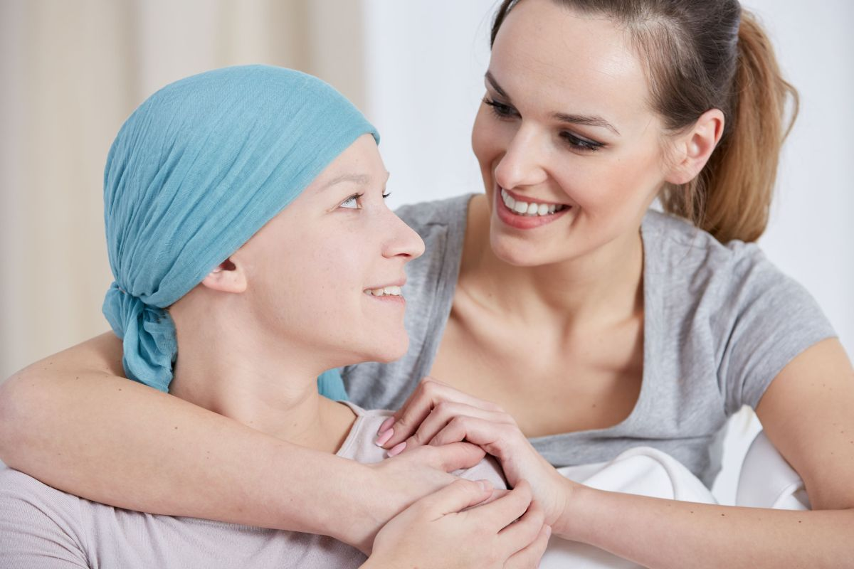 Hopeful cancer woman wearing headscarf, talking with friend - remote monitoring