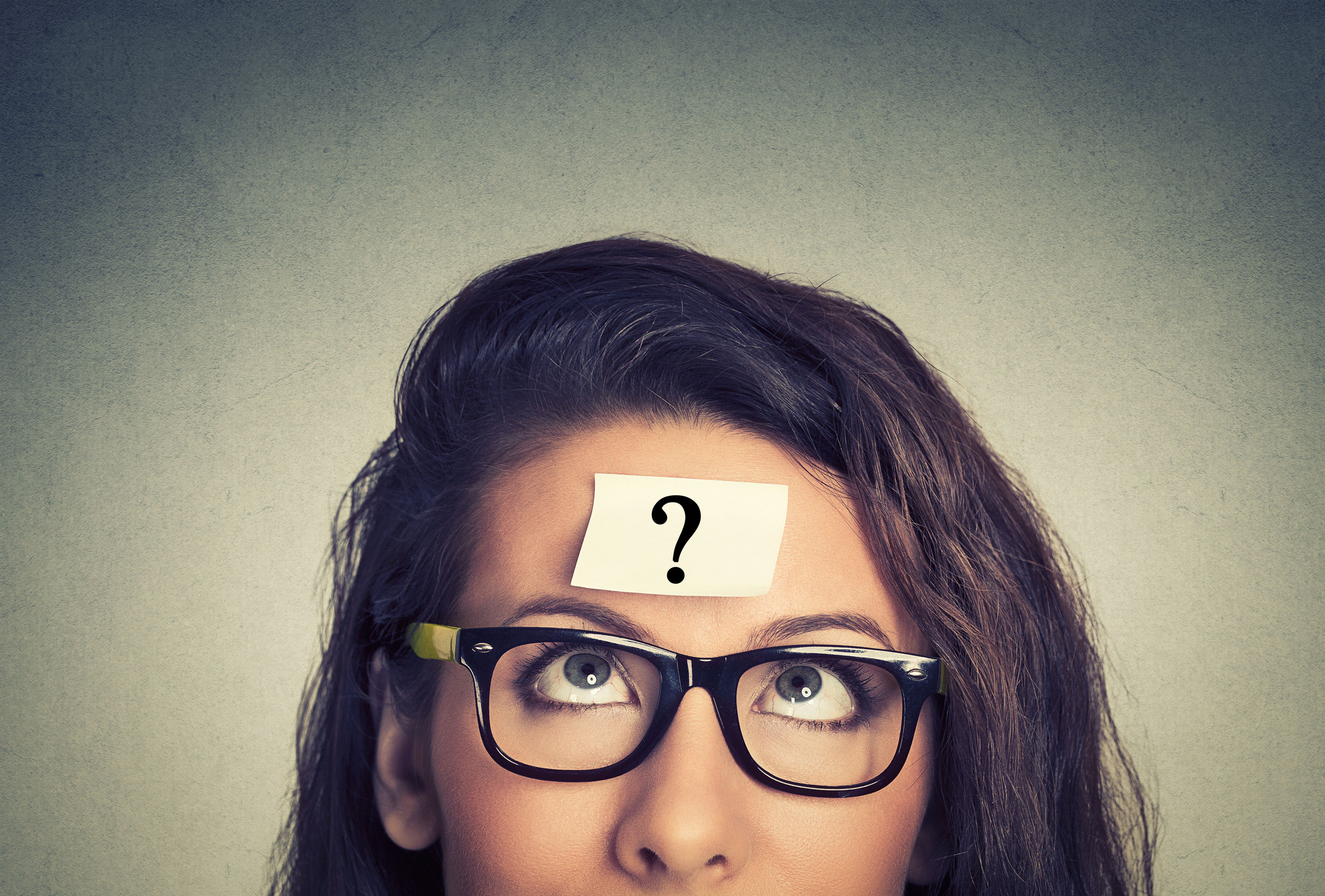 thinking woman with question mark on gray wall background - time management
