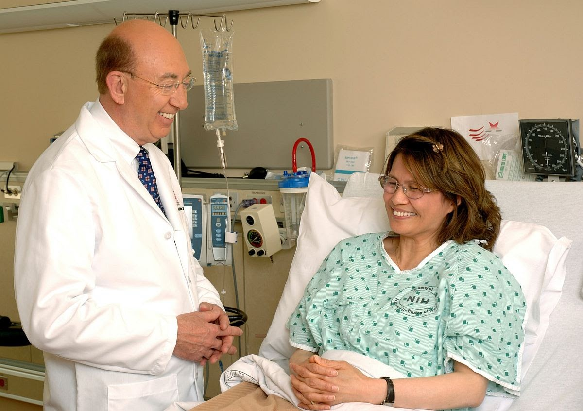 smiling doctor speaks with smiling patient in a hospital bed; concept: clinical quality management